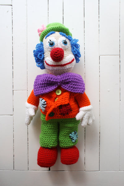 crocheted clown with purple bowtie, orange jacket, and red nose
