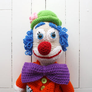 crocheted clown with blue hair, red nose, and purple bowtie