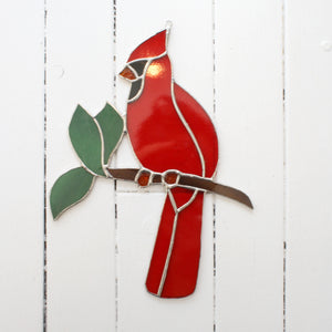stained glass cardinal bird perched on tree branch with three leaves