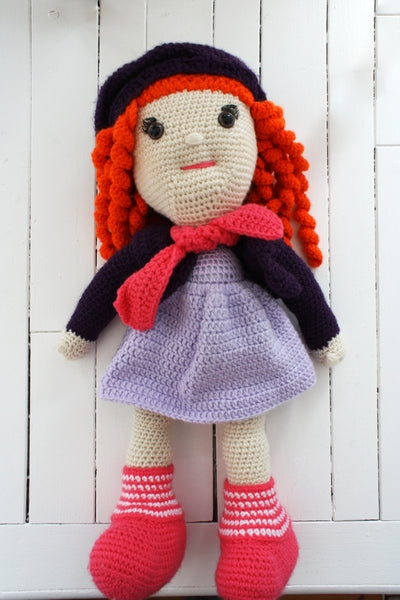 orange hair doll with purple outfit, pink scarf, and pink boots