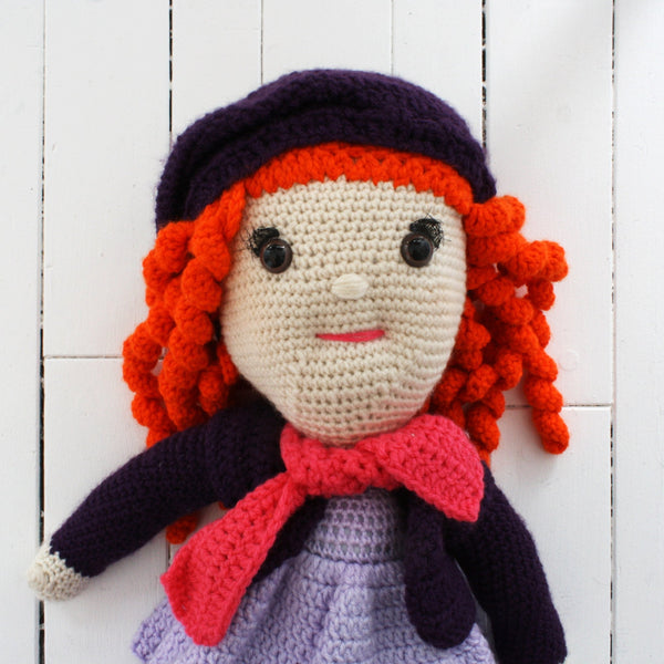 orange hair doll with purple outfit and pink scarf