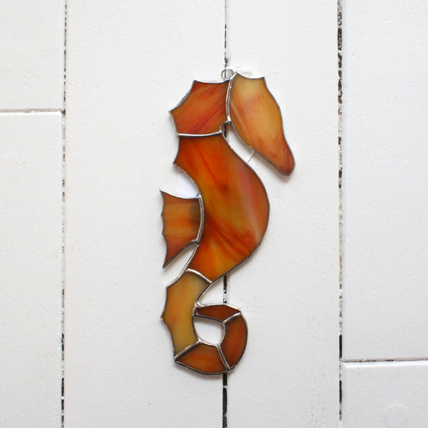 a stained glass seahorse with various shades of orange glass