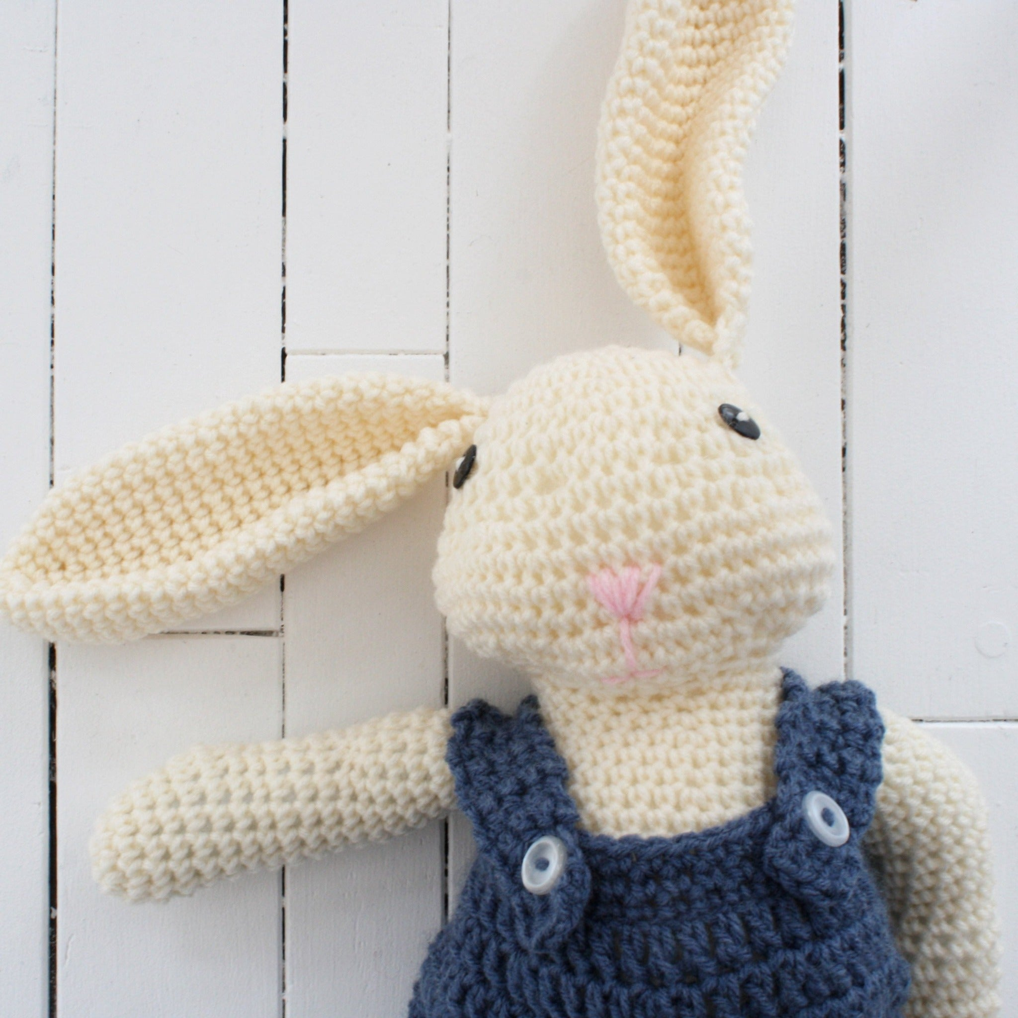 crocheted rabbit with blue overals and button eyes