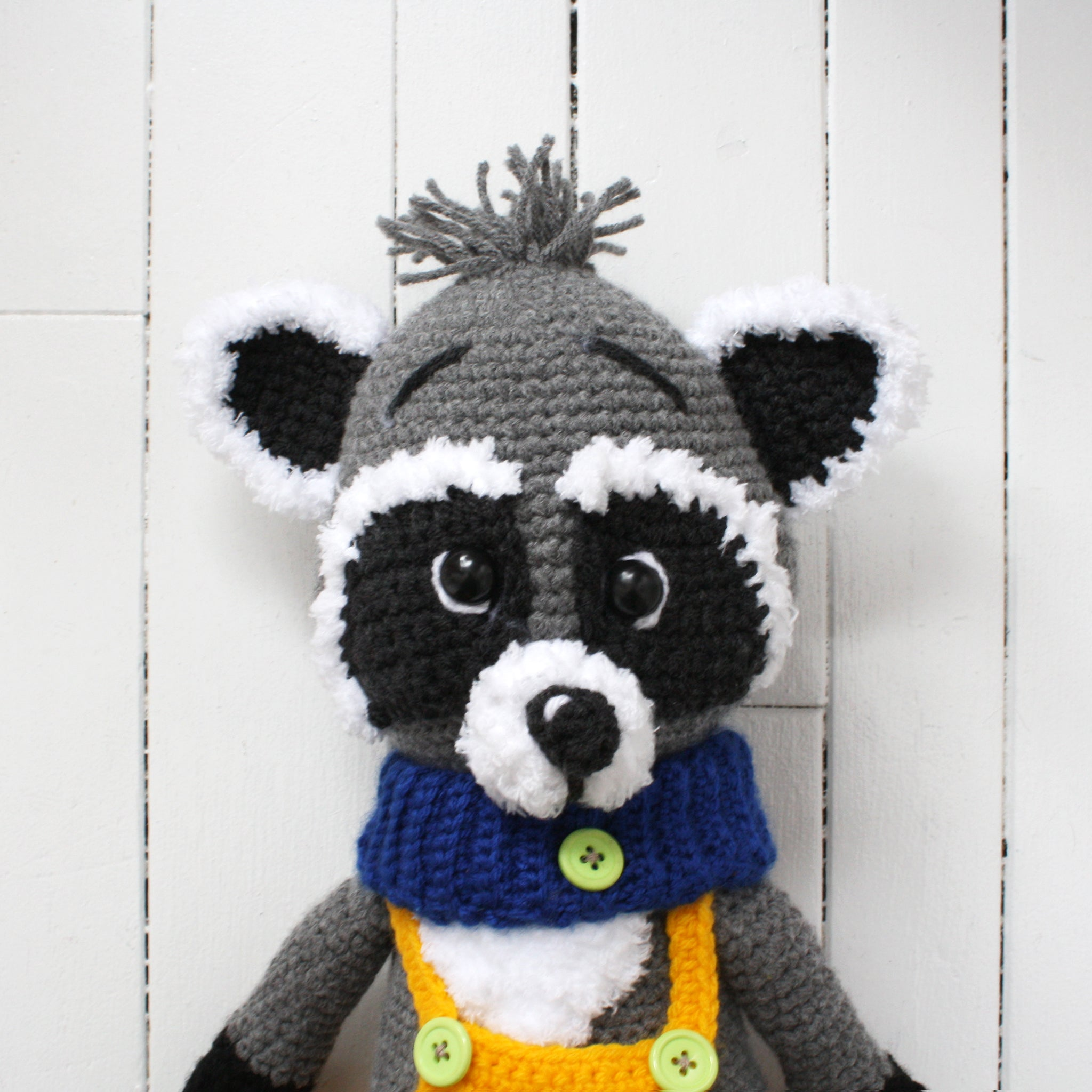Close up of a crocheted raccoon doll with blue scarf and yellow overalls