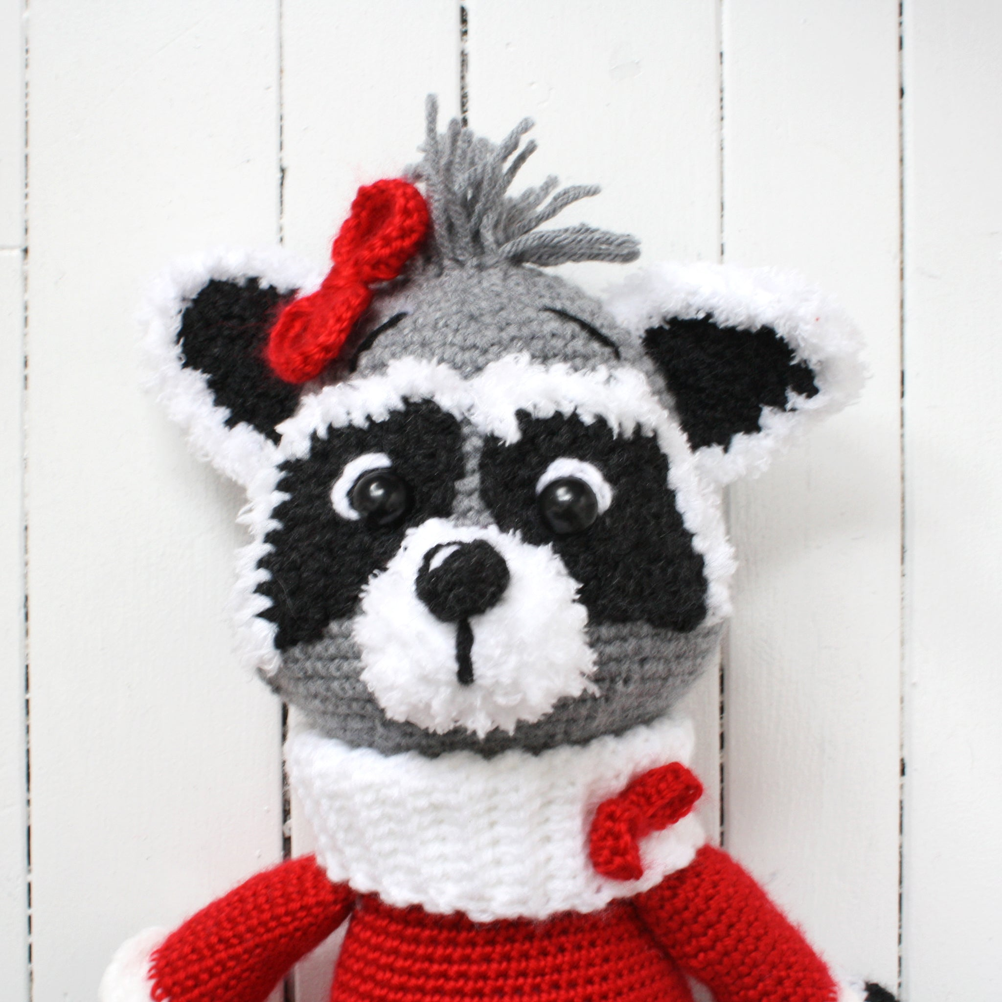 Close up of crocheted raccoon with red dress and bow