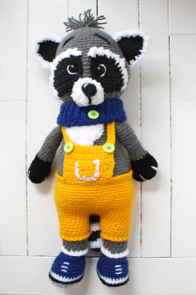 Full length image of a crocheted raccoon in yellow overalls.