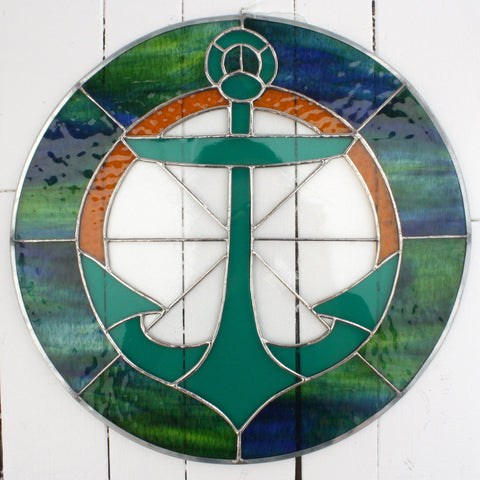 A large stained glass piece with green anchor made using several styles and colours of glass.