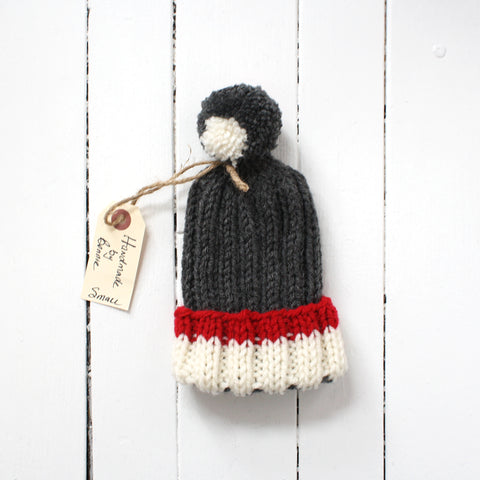 Small grey toque with white and red brim and tassel