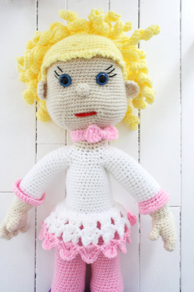 giant doll with yellow hair, blue eyes, and white dress