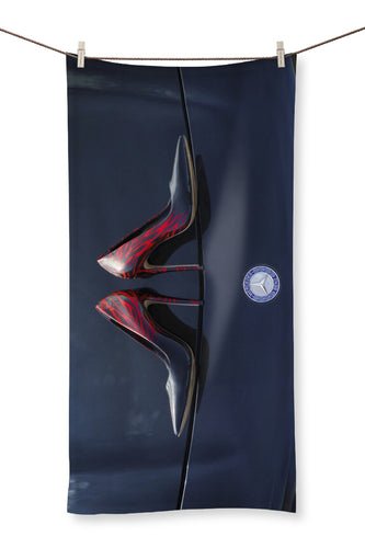 Towel showing a pair of Ladies high heeled red and black shoes on bonnet of a black Mercedes-Benz car