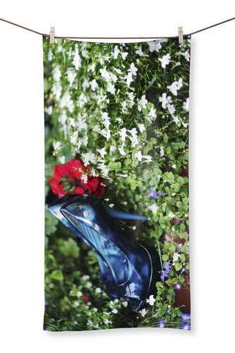 Towel  showing  pair of blue high heeled ladies shoes sitting in a flower bed, surrounded by red and purple flowers