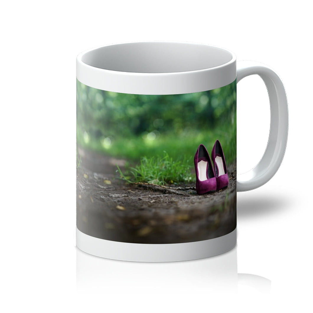 Tea or Coffee mug showing a pair of purple women's high heeled shoes alone on path in the woods