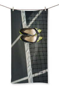 Towel showing Pair of women's high heeled shoes hanging over the top of a tennis net