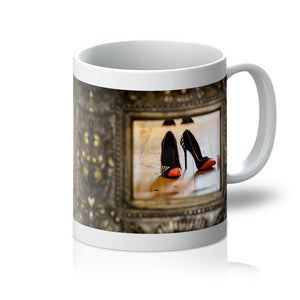 Tea or Coffee mug showing reflection in a mirror of pair of orange tipped black ladies high heeled shoes