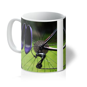 Tea or Coffee mug showing pair of purple high heeled ladies shoes hanging of spokes of the rear wheel of a bicycle