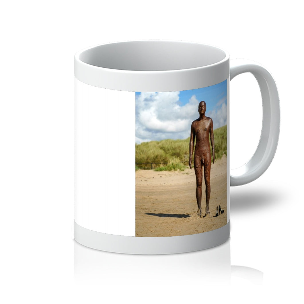 Tea or coffee mug showing Another Place statue by antony gormley with pair of high heal shoes on the beach