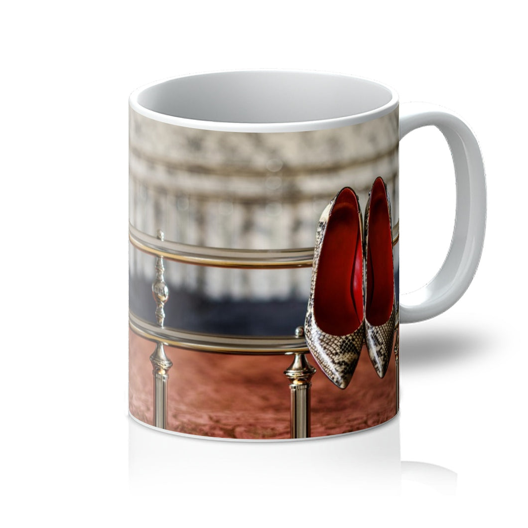 Tea or Coffee mug showing pair of ladies high heeled shoes, with  red interior and snake skin pattern, hanging off bed frame