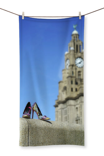 Towel showing Liverpool liver building with pair of multi-coloured high heeled shoes in foreground
