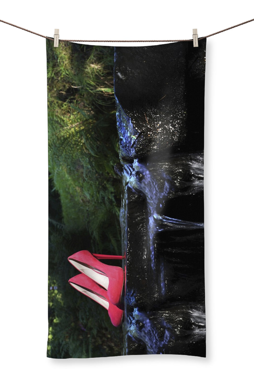 Towel showing pair of red ladies high heeled shoes placed on a rock in a river