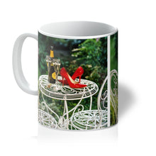 Load image into Gallery viewer, Tea or Coffee mug showing red high heeled shoes sitting on a garden table adjacent to a bottle of champagne, along with two filled champagne glass flutes