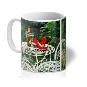 Tea or Coffee mug showing red high heeled shoes sitting on a garden table adjacent to a bottle of champagne, along with two filled champagne glass flutes