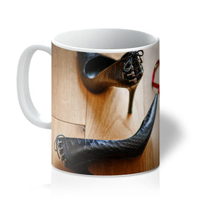 Tea or Coffee mug showing pair of red knickers abandoned on wooden floor next to pair of black high heeled ladies shoes