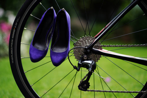 pair of purple high heeled ladies shoes hanging of spokes of the rear wheel of a bicycle