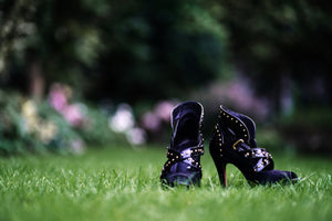 close up of pair of purple high heeled ladies ankle boots, on their own in a garden