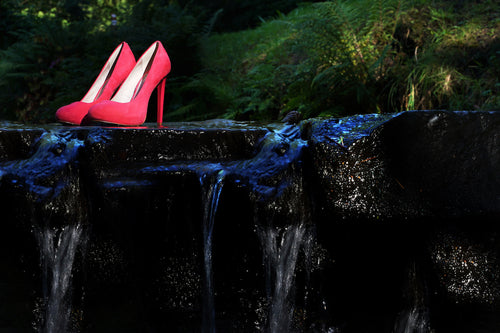 pair of red ladies high heeled shoes placed on a rock in a river