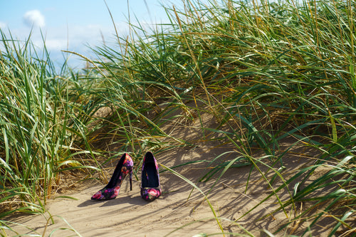 a pair of colourful ladies high heeled shoes on a grassy sand dune at the beach