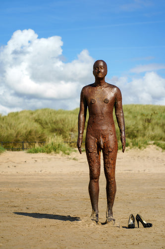 print showing Another Place statue by antony gormley with pair of high heal shoes on the beach