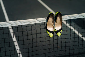Pair of women's high heeled shoes hanging over the top of a tennis net