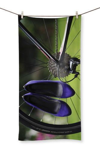 Towel showing pair of purple high heeled ladies shoes hanging of spokes of the rear wheel of a bicycle