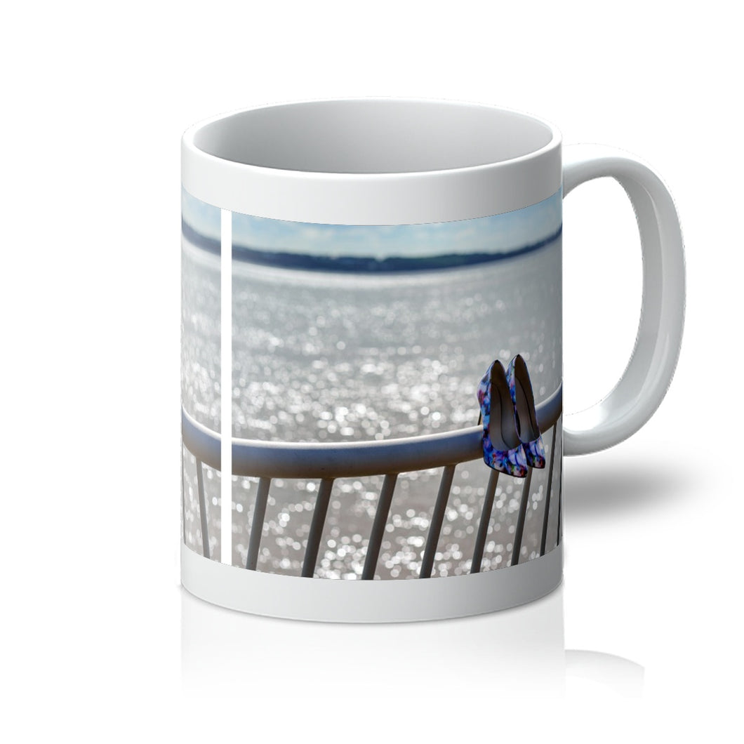 Tea or coffee mug containing image of women's shoes on railings next to River Mersey