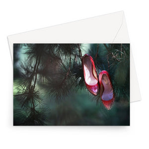 Greeting card with black border of pair of ruby coloured ladies high heeled shoes hung from branch of a green mistletoe tree