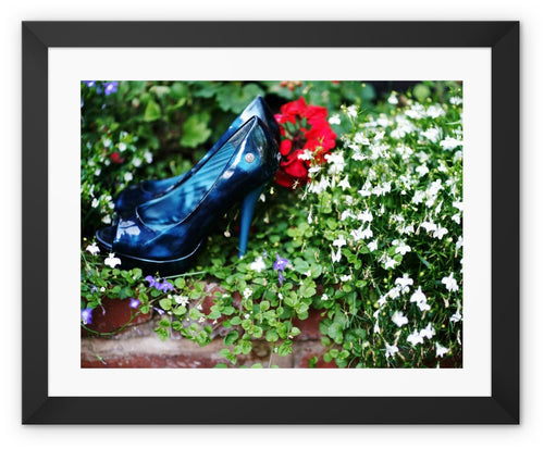 Framed print with black border showing pair of blue high heeled ladies shoes sitting in a flower bed, surrounded by red and purple flowers