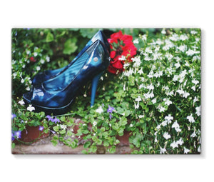 Canvas print with black border showing pair of blue high heeled ladies shoes sitting in a flower bed, surrounded by red and purple flowers
