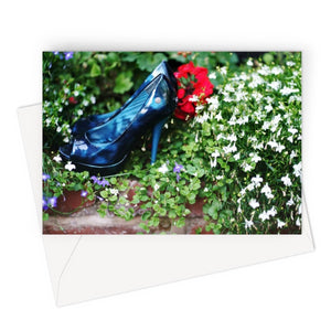 Greeting card  showing a pair of blue high heeled ladies shoes sitting in a flower bed, surrounded by red and purple flowers