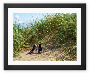 Framed print with black border showing a pair of colourful ladies high heeled shoes on a grassy sand dune at the beach