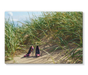 Canvas print with black border showing a pair of colourful ladies high heeled shoes on a grassy sand dune at the beach