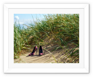 Framed print with white border showing a pair of colourful ladies high heeled shoes on a grassy sand dune at the beach