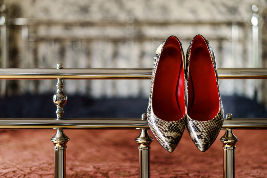 pair of ladies high heeled shoes, with  red interior and snake skin pattern, hanging off bed frame
