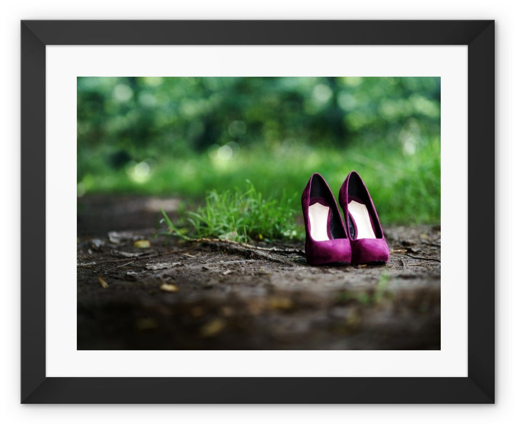 Framed print with black border showing a pair of purple women's high heeled shoes alone on path in the woods