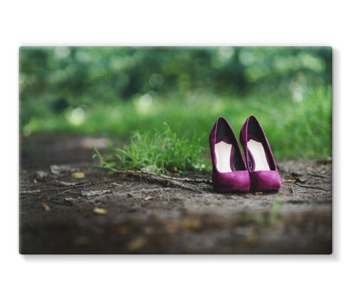 Canvas print showing a pair of purple women's high heeled shoes alone on path in the woods