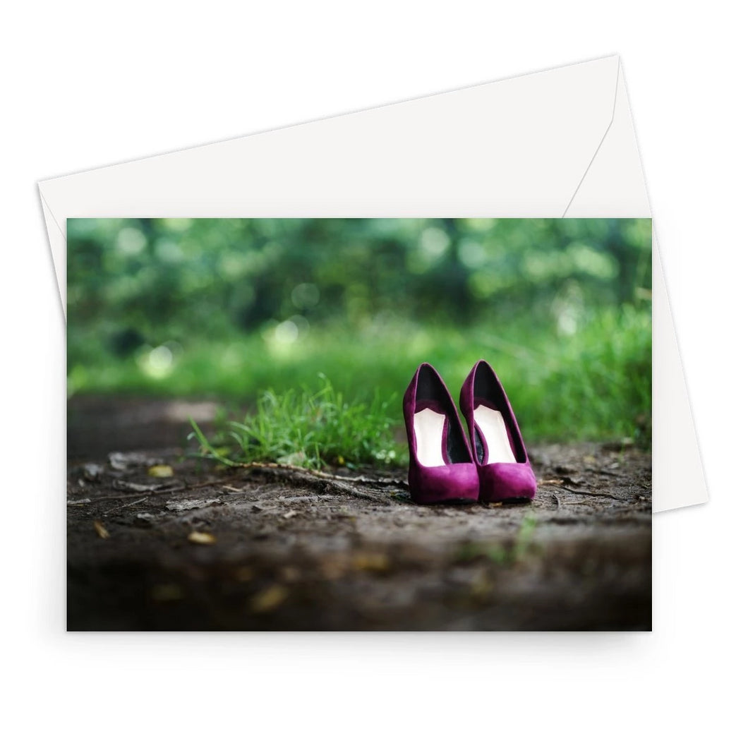 Greeting card showing showing a pair of purple women's high heeled shoes alone on path in the woods