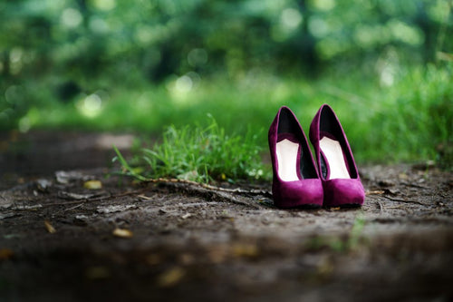 pair of purple women's high heeled shoes alone on path in the woods