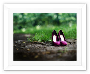 Framed print with white border showing a pair of purple women's high heeled shoes alone on path in the woods