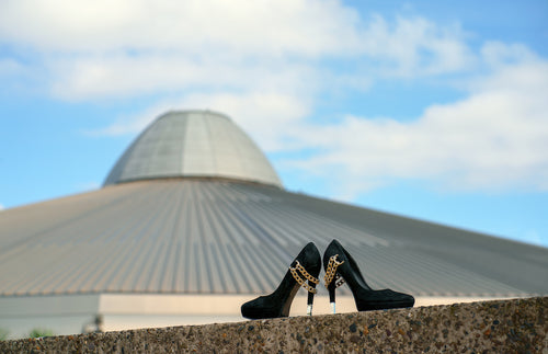 a pair of black high heeled ladies shoes in front of a building, shaped like a UFO spaceshipa