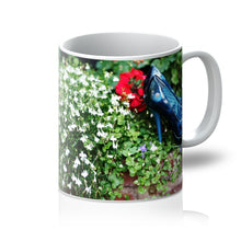Load image into Gallery viewer, Tea or  Coffee mug  showing  pair of blue high heeled ladies shoes sitting in a flower bed, surrounded by red and purple flowers