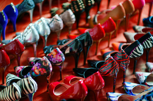 rows of women's high heel shoes on red floor
